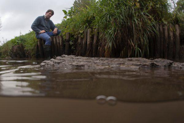 Meubelmaker Maarten Kien op De Schans waar hij een proef doet met boomstammen in water.
